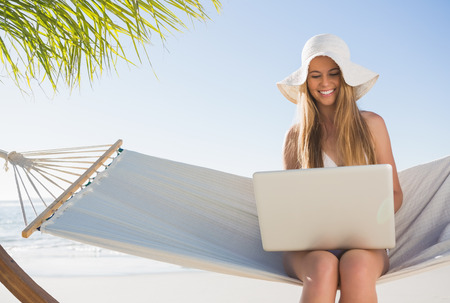 Happy blonde sitting on hammock using laptop at the beach photo