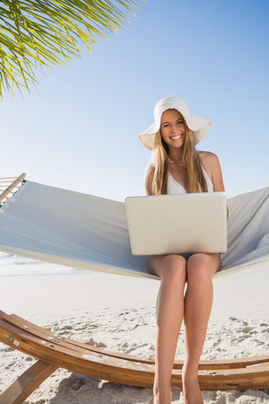 Smiling blonde sitting on hammock using laptop at the beach photo