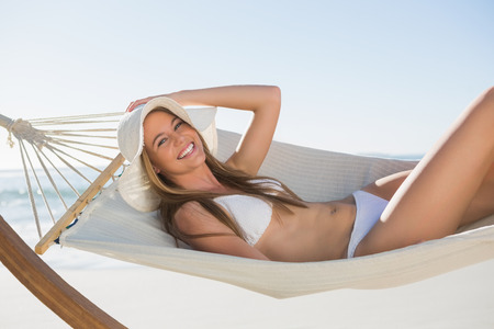 Cheerful blonde relaxing on hammock at the beach photo
