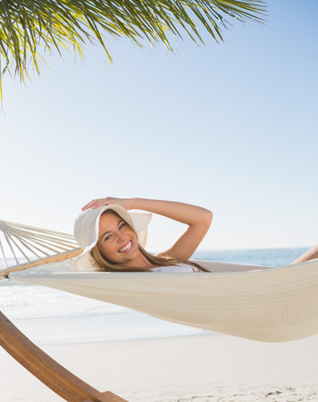 Smiling blonde relaxing on hammock at the beach photo