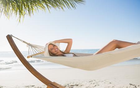 Woman wearing sunhat and bikini relaxing on hammock smiling at camera at the beach photo
