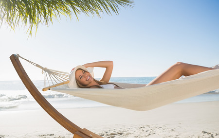 Woman wearing sunhat and bikini relaxing on hammock smiling at camera at the beach photo