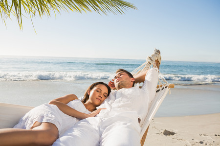 escapism: Calm couple napping in a hammock at the beach Stock Photo