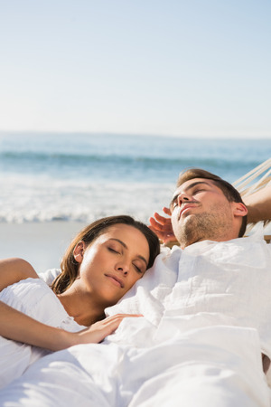 Peaceful couple sleeping in a hammock on the beach photo