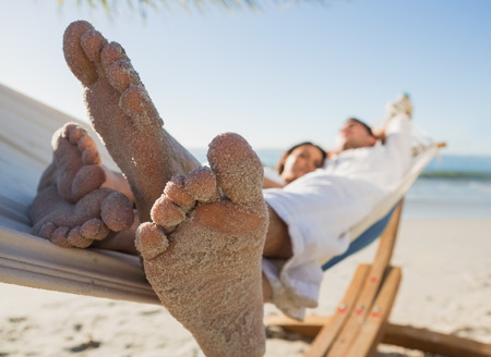 Close up of sandy feet of couple in a hammock on the beach photo