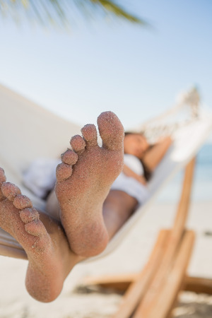 Close up of sandy feet of woman sleeping in a hammock on the beach photo