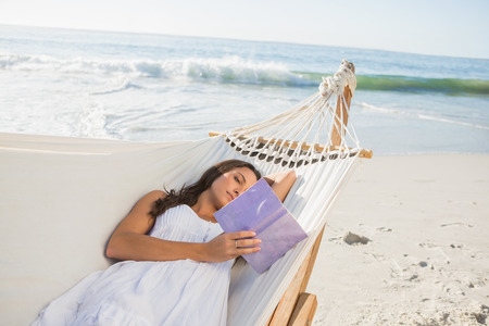 Woman lying on hammock reading book on the beach photo