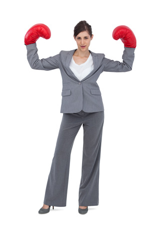 Businesswoman with boxing gloves on white background photo