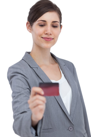 Confident businesswoman on white background holding credit card  photo