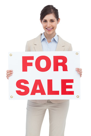 Smiling businesswoman with for sale sign on white background  photo