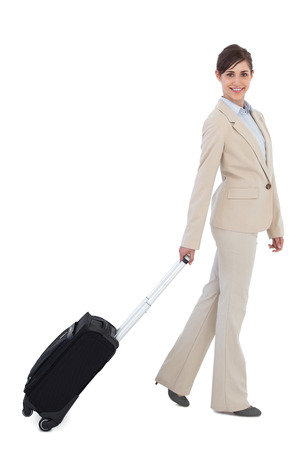 Smiling businesswoman pulling suitcase against white background photo