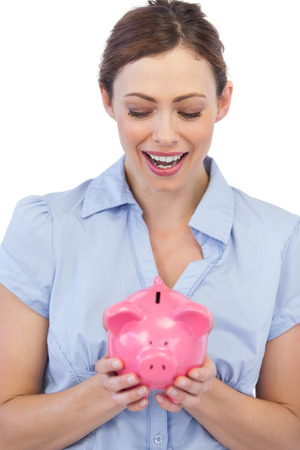 tied down: Astonished businesswoman posing with piggy bank against white background