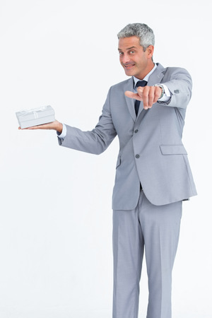 Confident businessman against white background pointing at camera photo