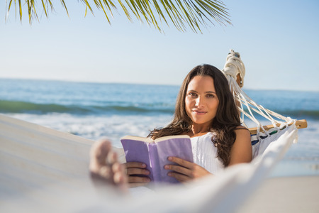 escapism: Peaceful woman lying on hammock reading book  on the beach Stock Photo