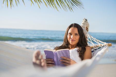Peaceful woman lying on hammock reading book  on the beach photo