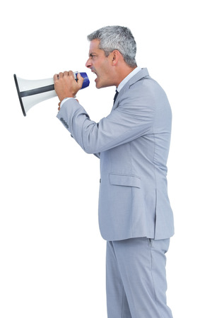 Furious businessman shouting in loudspeaker on white background photo