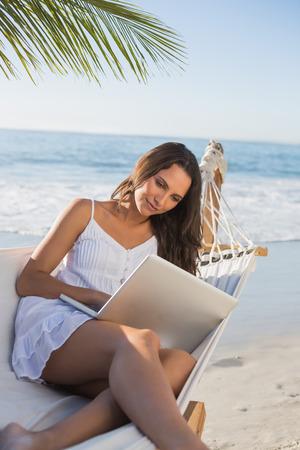 Brunette sitting on hammock using laptop on the beach photo