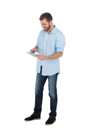 cut out device: Relaxed male model using his tablet pc on white background