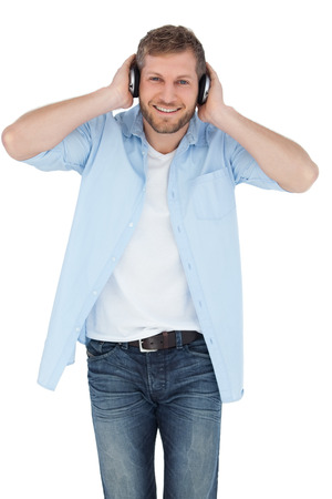 Trendy model on white background listening to music and looking at camera photo