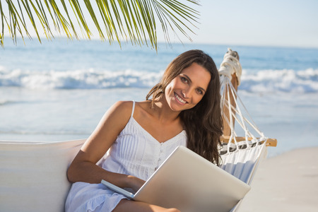 escapism: Pretty brunette sitting on hammock with laptop smiling at camera on the beach