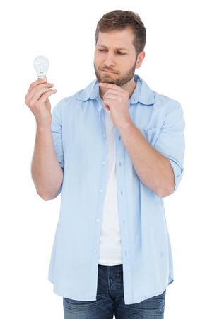 sceptical: Sceptical model on white background holding a bulb  Stock Photo