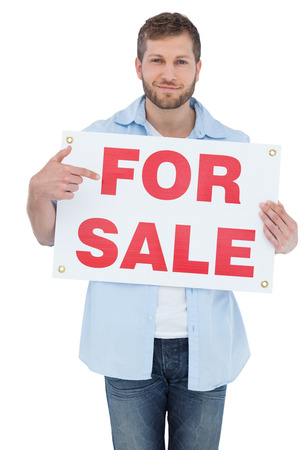 Trendy model on white background holding a for sale sign photo