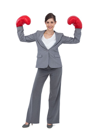 Businesswoman with red boxing gloves on white background photo