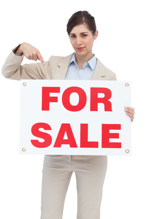 Estate agent holding and pointing to for sale sign on white background  photo