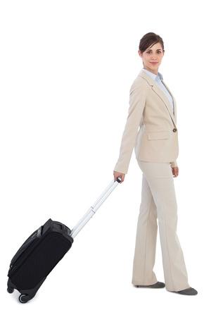 Businesswoman pulling suitcase against white background photo