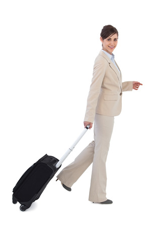 Cheerful businesswoman pulling suitcase against white background photo