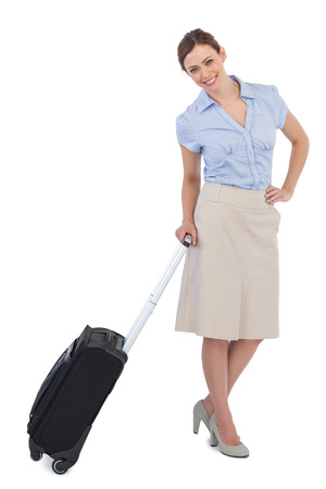Cheerful classy businesswoman against white background carrying suitcase photo