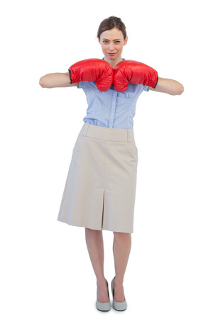 Tough businesswoman posing with red boxing gloves against white background photo