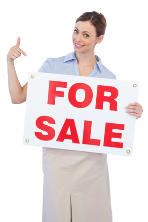 Happy estate agent posing and pointing to for sale sign on white background photo