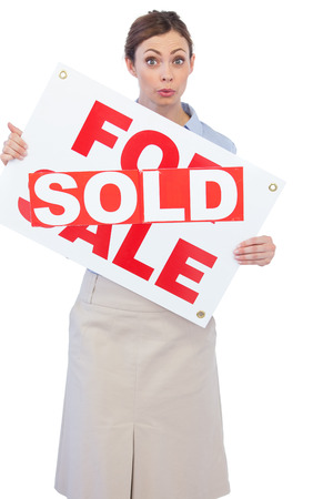 Estate agent showing for sale sign with sold sticker across it against white background photo