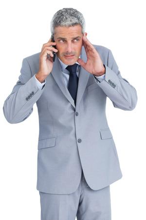 answering phone: Empresario atento tel�fono contestador contra el fondo blanco Foto de archivo