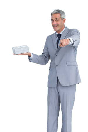 Good looking businessman against white background offering gift and pointing at camera photo