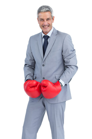 Cool businessman posing with boxing gloves on white background photo