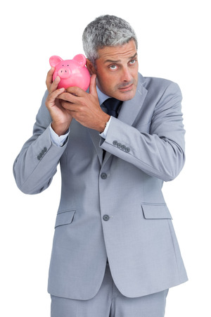 Doubtful businessman on white background holding piggy bank photo