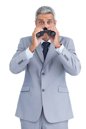 Curious businessman on white background observing with binoculars photo