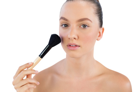 Model applying face powder with brush on white background photo