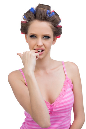 Model wearing hair curlers biting her finger sexily on white background photo