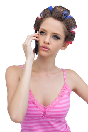 hair rollers: Modelo pensativo en rodillos de pelo en el tel�fono contra el fondo blanco Foto de archivo