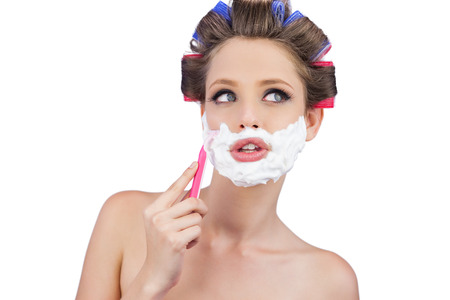 role reversal: Thoughtful woman in hair curlers posing with razor on white background