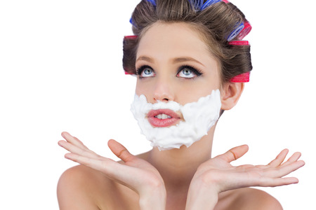 role reversal: Pensive woman posing with shaving foam on face on white background