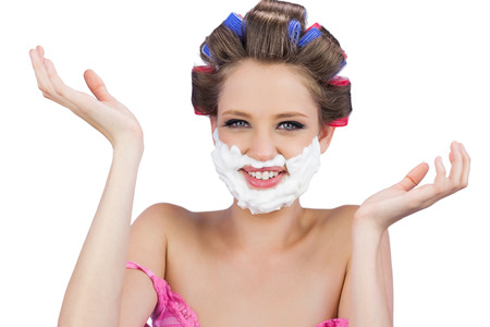 role reversal: Cheerful woman with hands up and shaving foam on face on white background