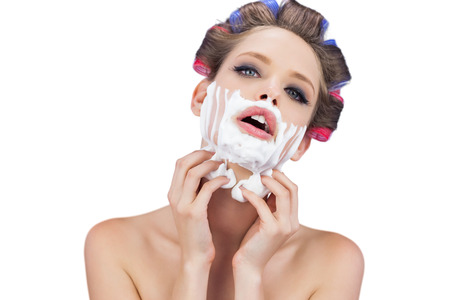 role reversal: Sensual young model with shaving foam looking at camera on white background