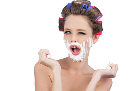 role reversal: Cheeky young model in hair curlers posing with shaving foam on white background