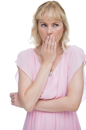 Blond woman putting her hand on her mouth on white background photo