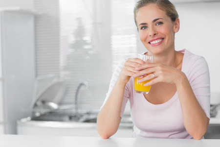 fair woman: Cheerful blonde having orange juice in her kitchen Stock Photo