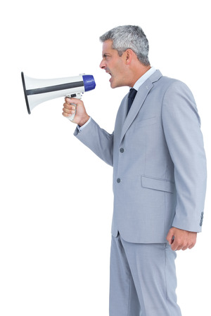 Businessman shouting in loudspeaker on white background photo